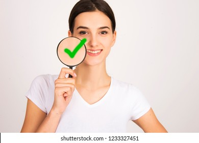 beautiful girl happy with perfect skin holding magnifier close up portratit smiling isolated od white