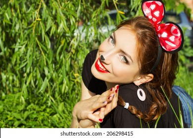 beautiful girl happy smiling in the costume of a mouse with a big red bow down on the grass in the Park