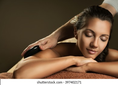 Beautiful girl has hot stone massage. Spa treatment.