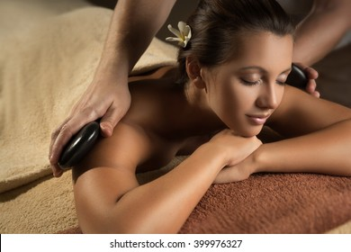 The beautiful girl has massage with hot stones. Luxury spa treatment.