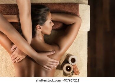 The beautiful girl has relaxing massage. Spa treatment. Candle setup