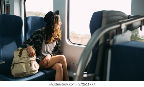 Beautiful girl in hat with a backpack sitting in the train. Traveling, journey.