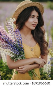 Beautiful girl in a hat with a bouquet of lupine flowers. A girl in a yellow dress, a straw hat, with a bouquet of lupins stands in a flower field. Young brunette girl. Summer time. Lupine field