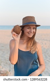 beautiful girl in a hat with a coconut in her hands against the background of the sea