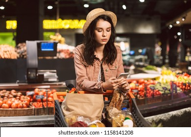 Beautiful girl in hat leaning on trolley full of products thoughtfully using cellphone in modern supermarket