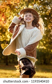 beautiful girl in a hat running in an autumn park and smiling