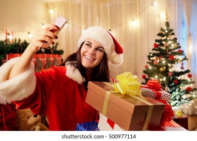 Beautiful girl in the hat of Santa Claus with gifts in his hands makes slefi telephone in the room with the decor,  tree, fireplace, gift boxes at Christmas, Happy New Year.