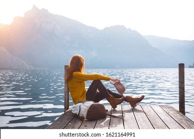 beautiful girl in a hat sitting on the pier at the lake bank and mountains in the background