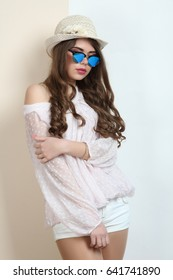 Beautiful girl in a hat and sunglasses on a white and beige background