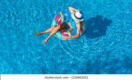 Beautiful girl in hat in swimming pool aerial top view from above, woman relaxes and swims on inflatable ring donut and has fun in water on family vacation, tropical holiday resort