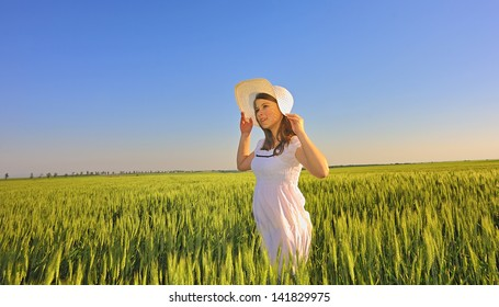 beautiful girl with hat in wheat field