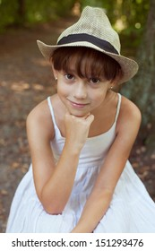 Beautiful girl in hat and white dress