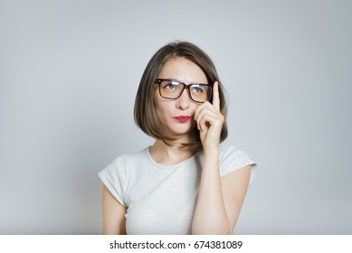 Beautiful girl have a good idea, wears glasses, isolated on gray background