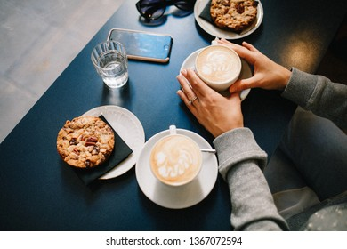 Beautiful girl have a nice time and morning drinking cappuccino in nice coffe shop sitting at the wooden table and her friend drinks tea
