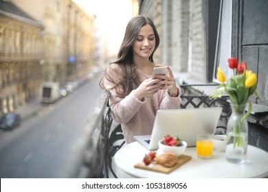 Beautiful girl having breakfast in the balcony, while using her laptop