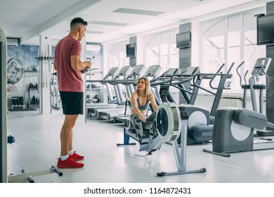 Beautiful girl having chat with frend after hardly training on rowing machine in the gym.