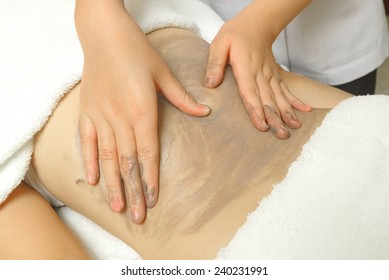 Beautiful girl having clay body massage