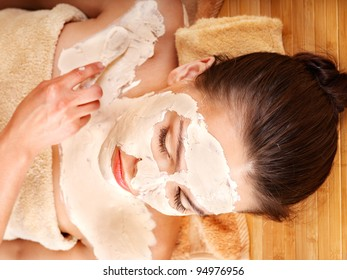 Beautiful girl having clay body mask apply by beautician.