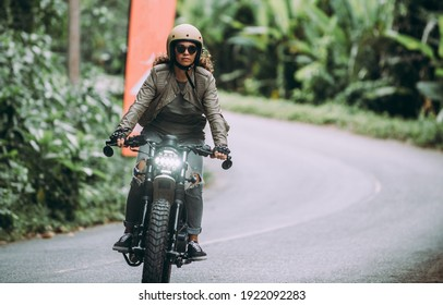 Beautiful girl having fun driving her custom cafe racer motorcycle