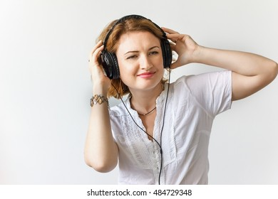 � Beautiful girl with headphones listening to music and dancing in a white shirt, soft focus, studio