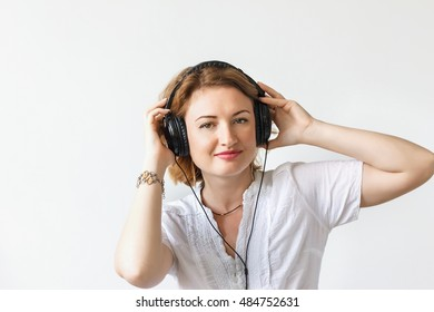Beautiful girl with headphones listening to music and dancing in a white shirt, soft focus, studio