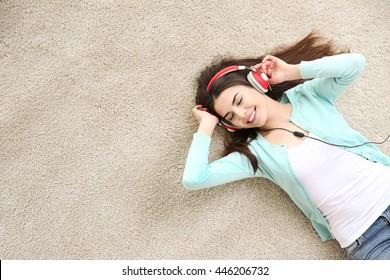 Beautiful girl with headphones lying on floor