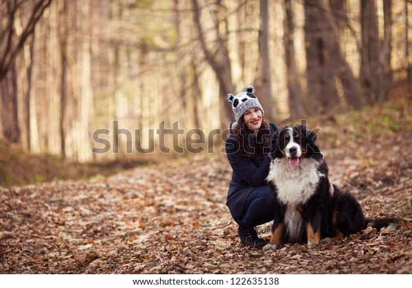 Beautiful Girl with her dog in autumn forest. Bernese Mountain Dog.