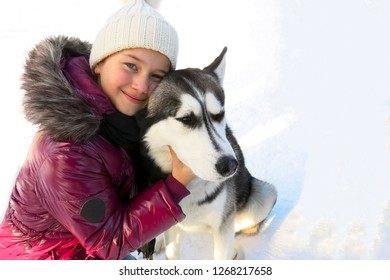 Beautiful girl and her dog husky in winter park. Husky with different eye color.