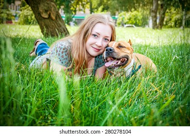 Beautiful girl and her dog in summer park