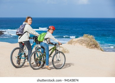 Beautiful girl and her grandmother on bikes on the beach. Lanzarote