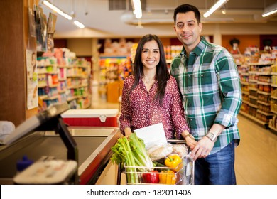 Beautiful girl and her partner about to pay for their food at the checkout counter