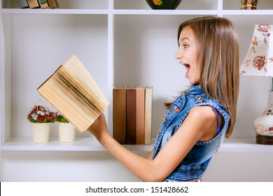 beautiful girl in her room with a book in his hands. surprise