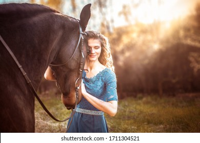Beautiful girl with her wavy hair in a blue dress hugs a horse and smiles. A bay horse stands in a green meadow in the sunset. Magical, fabulous fantasy photography.