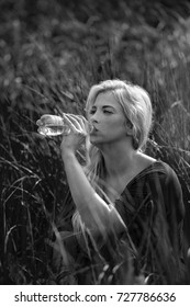 Beautiful girl hidden in fresh grass drinking healthy water with minerals and  microelements