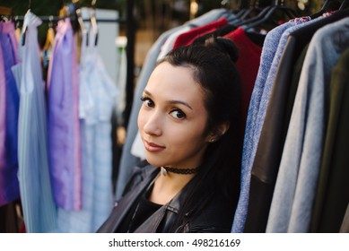 Beautiful girl hides in clothes on a street fair