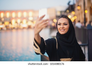 Beautiful girl with hijab taking smiling selfie outside in the city near the river.