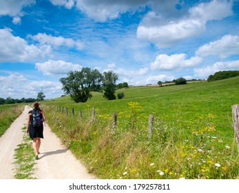Beautiful girl hiking in a rural landscape in the summer