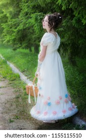 Beautiful girl in an historical bride dress with a wicker basket in her hands in a spring garden for a walk.