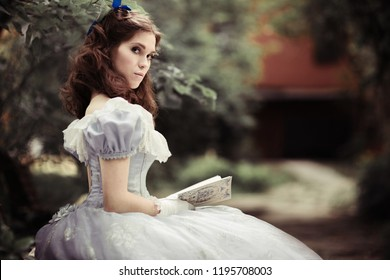 beautiful girl in historical dress, gloves, with a book in her hands sitting on the bench