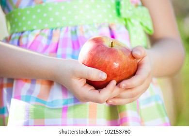 A beautiful girl holding an apple in his hand/Girl and apple/Apple