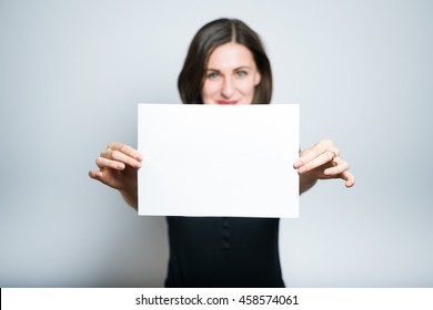 beautiful girl holding a blank for insert your text or product, studio photo isolated on a gray background
