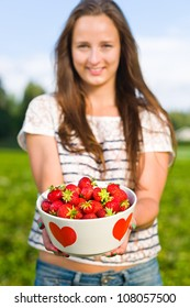 Beautiful girl holding a bowl of fresh strawberries, focus on the bowl