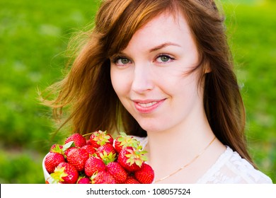 Beautiful girl holding a bowl of fresh strawberries, focus on the eyes