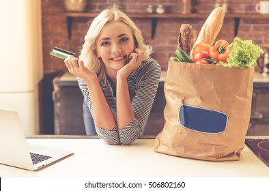 Beautiful girl is holding a credit card, leaning on table near paper shopping bag with food and a laptop, looking at camera and smiling