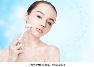 Beautiful girl holding drainage massage face roller on on blue bokeh background