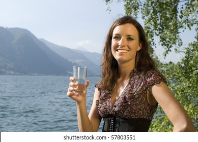 Beautiful girl holding a glass of water at the lake of Zell am See, Austria