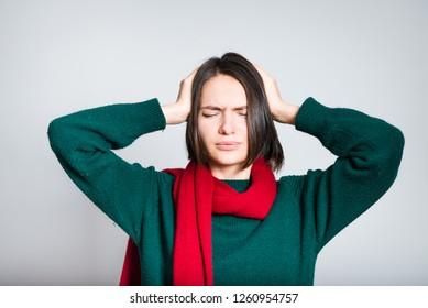 beautiful girl holding with headache, migraine, red scarf for new year and christmas, close-up over gray background