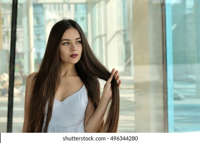 Beautiful girl holding her hair on a bent arm. She has long brown hair and well-groomed skin. Portrait against glass and metal.