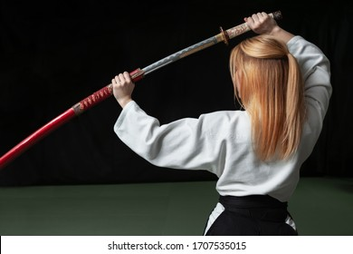 Beautiful girl holding a japanese katana sword in her hands above her head