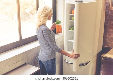 Beautiful girl is holding a jug of juice and smiling while standing near the open fridge in kitchen at home